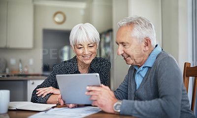 Buy stock photo Cropped shot of a senior couple going through their finances while sitting at the dining room table