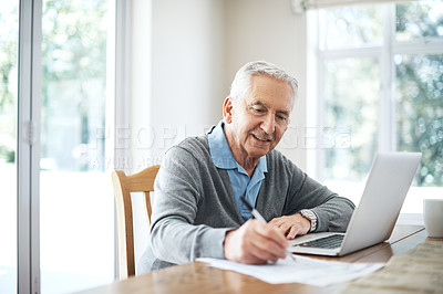 Buy stock photo Cropped shot of a senior man going through his finances while sitting at the dining room table