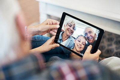 Buy stock photo Shot of an adorable little girl using a digital tablet with her grandparents at home