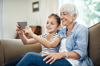 Buy stock photo Shot of an adorable little girl taking a selfie with her grandmother at home