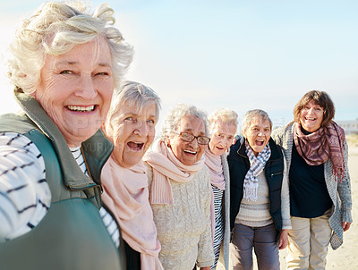 Buy stock photo Shot of a group of seniors spending the day on the beach