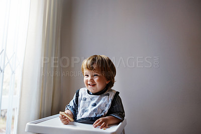 Buy stock photo Shot of an adorable little boy sitting in his high chair