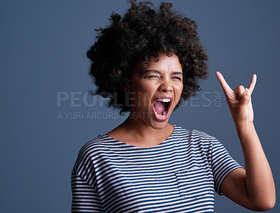 Buy stock photo Studio shot of an attractive young woman making a rock 'n roll gesture against a blue background