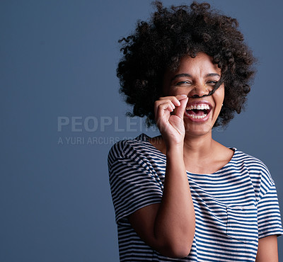 Buy stock photo Studio shot of an attractive young woman playing with her hair against a blue background