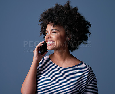 Buy stock photo Studio shot of an attractive young woman using a mobile phone against a blue background