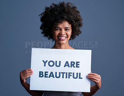 """Buy stock photo Studio shot of an attractive young woman holding a placard with the words """"you are beautiful"""" on it"""