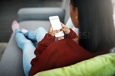 Buy stock photo Rearview shot of an unrecognizable woman using a cellphone while chilling on the sofa in the living room at home