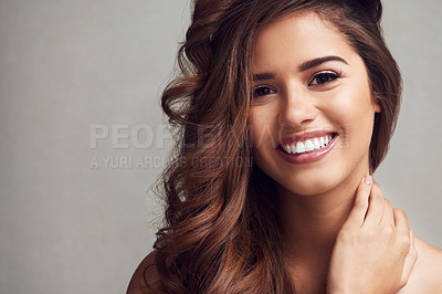 Buy stock photo Studio shot of a young beautiful woman with long gorgeous hair posing against a grey background