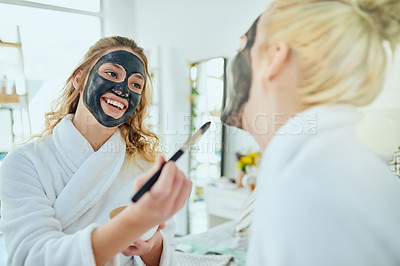 Buy stock photo Cropped shot of an attractive young woman applying a face mask to her friend's face during a girls' weekend at home