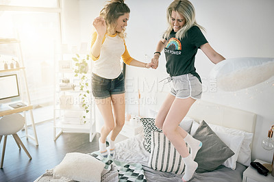 Buy stock photo Shot of two young women jumping on a bed together