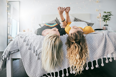 Buy stock photo Shot of two friends lying together on the edge of a bed