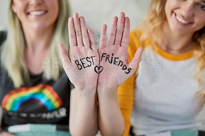 Buy stock photo Shot of two young friends showing the palm of their hands with writing on it