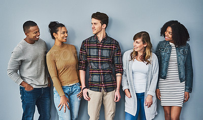 Buy stock photo Studio shot of a diverse group of young people standing together against a gray background