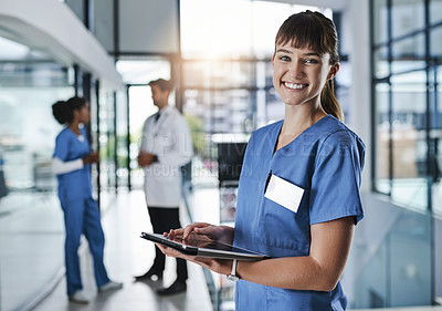 Buy stock photo Shot of a young doctor using a digital tablet in a hospital with her colleagues in the background