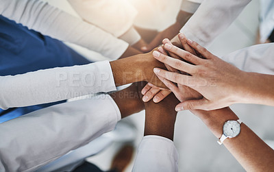 Buy stock photo Shot of a group of doctors joining their hands in solidarity at a hospital