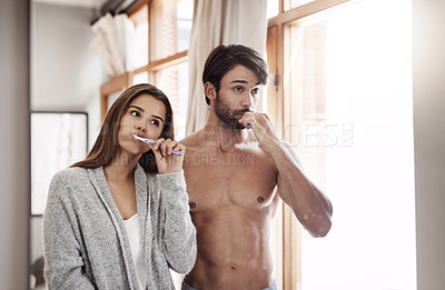 Buy stock photo Shot of a young couple brushing their teeth together at home