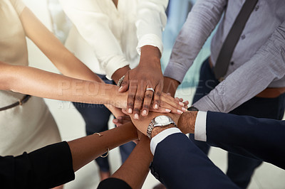 Buy stock photo Closeup shot of an unrecognizable group of businesspeople joining their hands together in a huddle in an office