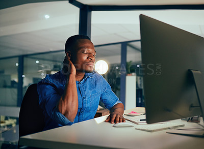 Buy stock photo Cropped shot of a young handsome businessman experiencing body discomfort while working late in the office