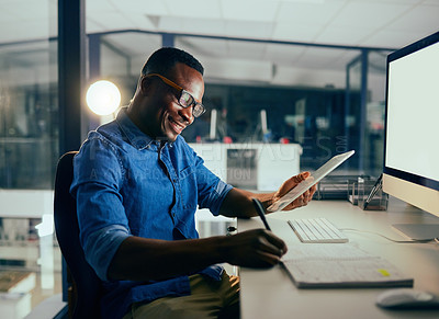 Buy stock photo Cropped shot of a young handsome businessman using a tablet while working late in the office