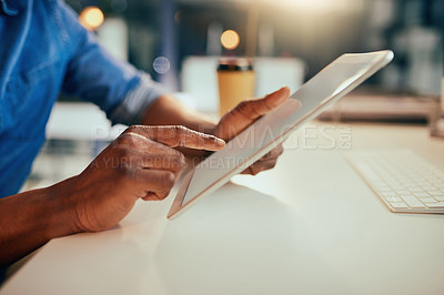 Buy stock photo Cropped shot of an unrecognizable businessman using a tablet while working late in the office