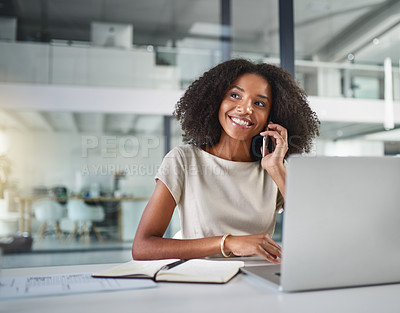 Buy stock photo Cropped shot of an attractive young businesswoman making a phonecall while working on a laptop in her office