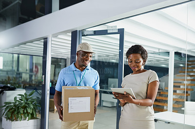 Buy stock photo Shot of a young woman using a digital tablet when receiving a delivery from the courier in an office