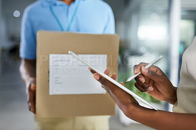 Buy stock photo Cropped shot of a woman using a digital tablet to sign for a delivery in an office