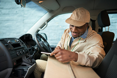 Buy stock photo Shot of a delivery man using a digital tablet in a van