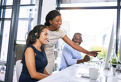 Buy stock photo Shot of a young woman helping her colleague in a modern call centre