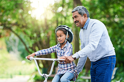 Buy stock photo Cropped shot of an adorable little girl learning how to ride a bike while enjoying the day outdoors with her granddad