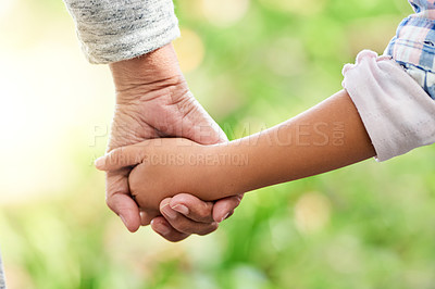 Buy stock photo Cropped shot of an unrecognizable little girl holding her grandmother's hand while enjoying the day outdoors