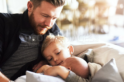 Buy stock photo Shot of young man hanging out on the sofa with his two little boys at home during the day