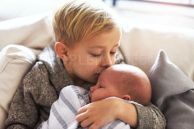 Buy stock photo Shot of a cheerful little boy holding his little infant brother and giving him a kiss on the forehead while being seated on a sofa at home during the day