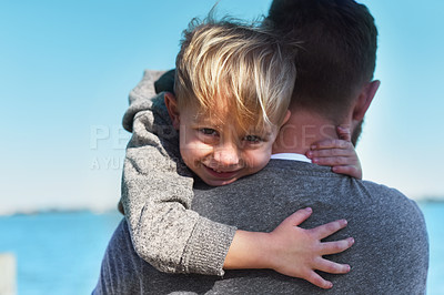 Buy stock photo Portrait of a cheerful little boy being held by his father while they stand next to a beach outside during the day
