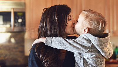 Buy stock photo Shot of a cheerful little boy giving his mother a little kiss at home during the day