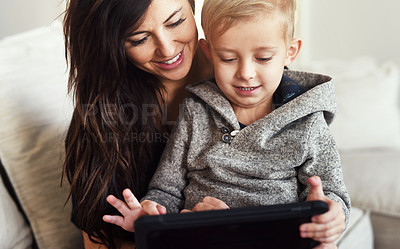 Buy stock photo Shot of a carefree young woman browsing on a digital tablet with her little boy while being seated on a sofa at home during the day