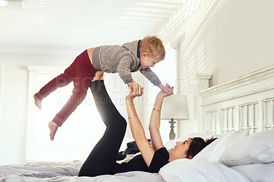 Buy stock photo Shot of a cheerful little boy being lifted up in the air by his mother's legs in the bedroom at home during the day