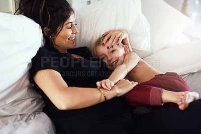 Buy stock photo Shot of a cheerful little boy and his mother hanging out on the bed at home while relaxing during the day