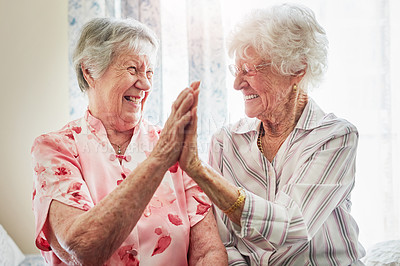 Buy stock photo Shot of two happy elderly women giving each other a high five together at home