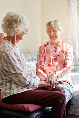 Buy stock photo Shot of two happy senior women chatting in a retirement home