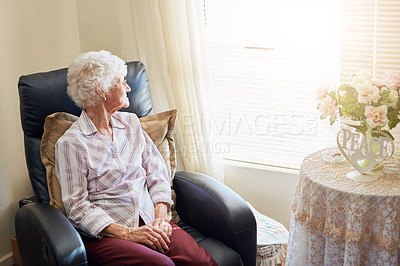 Buy stock photo Shot of an elderly woman relaxing on a chair at home and looking thoughtfully out the window