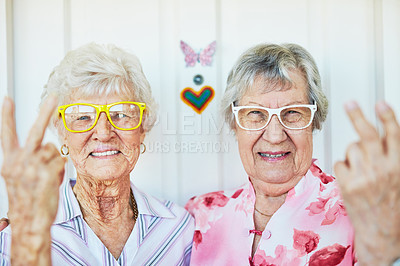 Buy stock photo Portrait of two happy elderly women wearing funky glasses at home