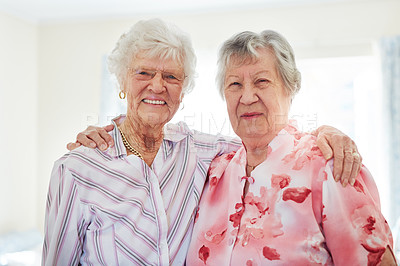 Buy stock photo Portrait of two happy elderly women embracing each other at home