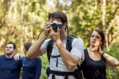 Buy stock photo Shot of a man using his camera while out hiking with others