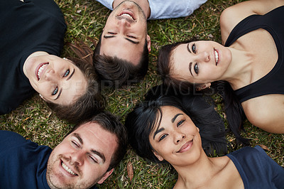 Buy stock photo Portrait shot of a group of friends lying together on the grass
