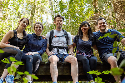 Buy stock photo Rearview shot of a group of friends taking a break while hiking