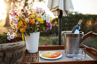 Buy stock photo Still life shot of a bottle of wine and slices of fruit on a tray outdoors