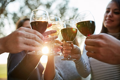 Buy stock photo Shot of a group of friends making a toast together outdoors