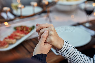 Buy stock photo Closeup shot of people holding hands in prayer before having a meal together