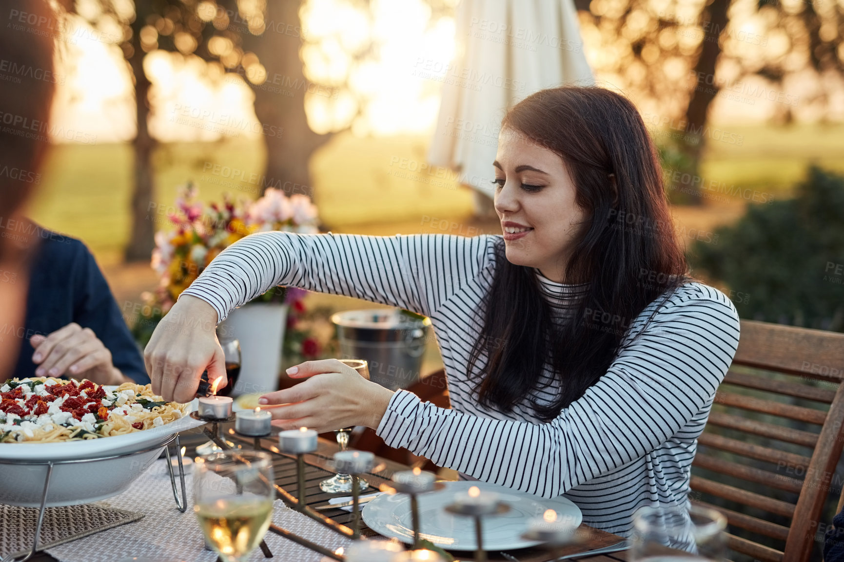 Buy stock photo Shot of a young woman lighting candles on the dinner table outdoors